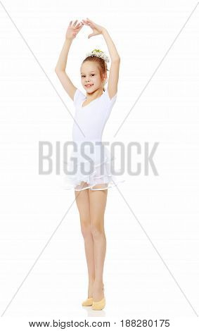 Cheerful little girl gymnast in a white sports dress, posing in front of the camera.Isolated on white background.