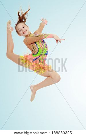 Beautiful little girl gymnast dressed in sports swimsuit for competitions, performs a jump.On the pale blue background.