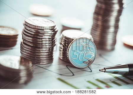 Financial investment concept with coins and business chart and pen