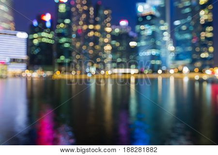 Blurred bokeh light Singapore central business downtown with reflection night view abstract background