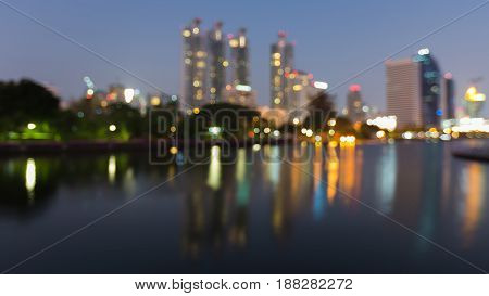 Nigh reflection blurred bokeh light office building in public park abstract background