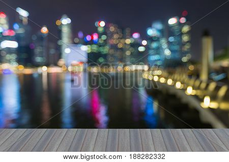 Opening wooden floor Blurred bokeh city of Singapore city night light abstact background