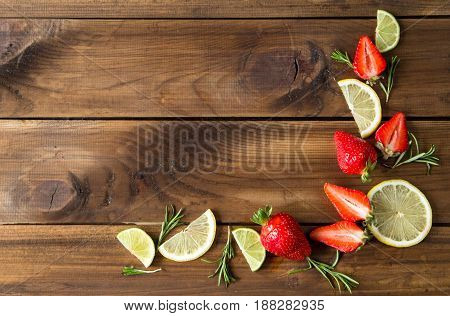 Fresh strawberries, lime slices and rosemary on old wooden background. top view. space fot text