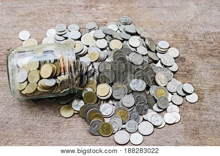 Coins in glass jar with investment financial concept and stack money on wood background
