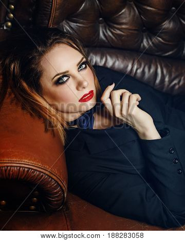 Young attractive girl in a jacket and bow tie. Femme fatale. Evening makeup smokey eye. She lies on a leather couch and looks at the camera.