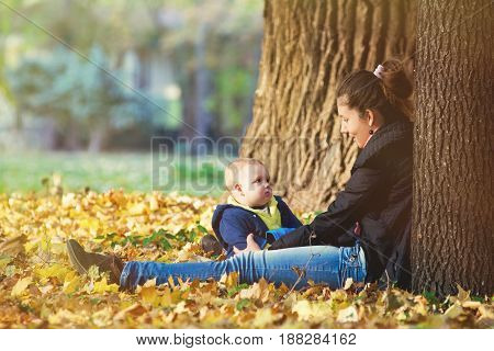 Young mother and her toddler baby boy have fun in autumn park with falling leaves. Happy family concept. Mom with her years old son walking outdoors in autumn