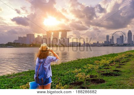 Young woman traveler with sky blue backpack and hat holding the map with singapore city downtown background. Traveling in singapore at sunset times