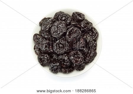 Bowl of dried plums isolated on white background. Top view