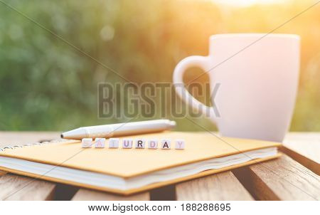 Saturday written in letter beads and a coffee cup on table