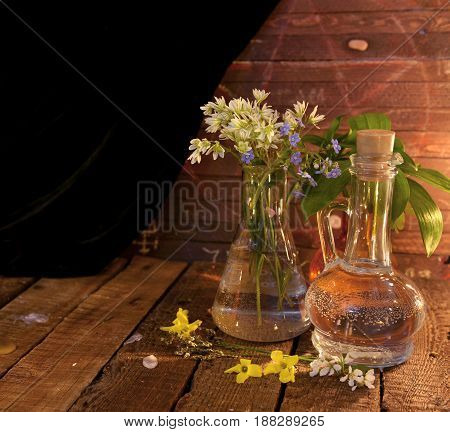 Still life with flowers in old glass bottles. Alternative medicine vintage concept