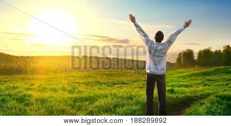 Happy and successful man raising hand in from of the sun and on the fields. Inspired concept, positivity, hope