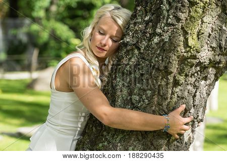 Blonde woman hugging a tree in park. Young girl resting in nature leaned against a tree