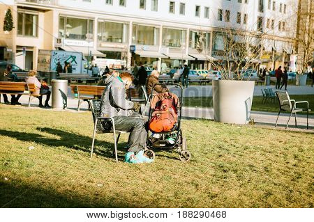 Munich, Germany, December 29, 2016: The father walks with a small child in a stroller in a park in the center of Munich. Care, outdoor recreation, childhood.