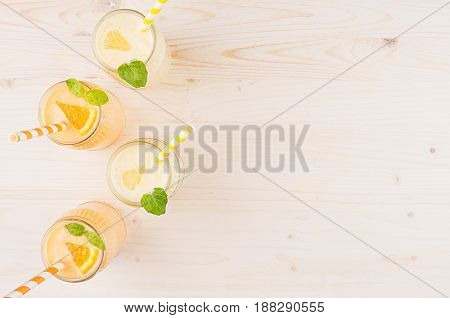 Freshly blended orange and yellow lemon smoothie in glass jars with straw mint leaf top view. White wooden board background copy space.