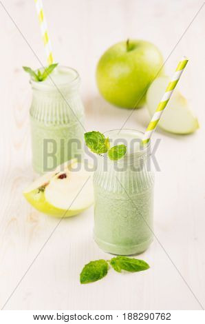 Freshly blended green apple fruit smoothie in glass jars with straw mint leafs apples. White wooden board background copy space.