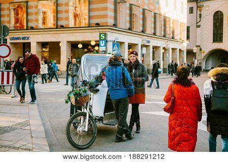Munich, Germany, December 29, 2016: A man on a date with a woman in the center of Munich in the Marienplatz square. Tender feelings, relationship between a man and a woman.