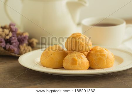 Homemade cream puffs filled with vanilla custard cream. Choux cream on white plate put on rustic wood table serve with tea in white pot or cup of coffee. Cream puffs or choux cream or eclairs.