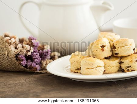 Homemade raisin scones serve with homemade strawberries jam,clotted cream and tea.Scones is English traditional pastry for afternoon tea,cream tea.Delicious scones Devon shire or Cornish cream style. Raisin scones on white plate put on rustic wood table.