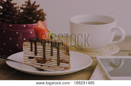 Homemade chocolate crepe cake on white plate put on rustic wood table cover cake with whipped cream topping with dark chocolate sauce,mint and lovely strawberry delicious dessert for coffee break or tea time fresh for summer.