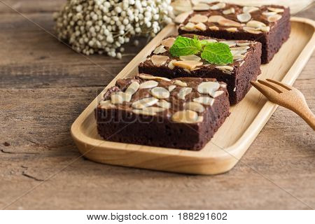 Homemade dark chocolate brownies topping with almonds slices decorated with mint. Fudge brownies on wood plate put on rustic wood table.Bitter,sweet and fudge.Brownie is one type of chocolate cake. Chocolate brownies by selective focus.