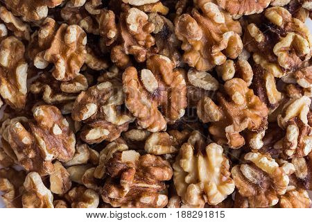 Baked walnuts for snack and bakery. Walnuts is good for health, diet food, raw material or ingredients for cooking.Close Up view, top view of baked walnuts with warm tone style for background,macro concept.