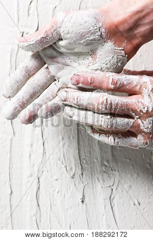 Worker hands in white stucco background, flat lay. Repair, construction work, building, plastering concept