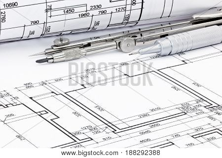 Pencil With Drawing Compass And Rolled Plans Of Architectural Blueprints Closeup