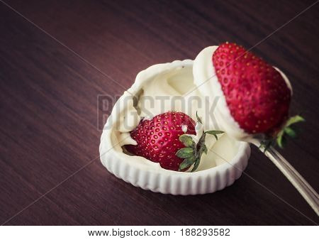 A strawberry with cream on a teaspoon very tasty food.