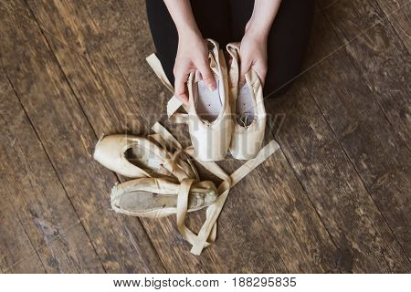 Ballerina sits on the wooden floor and holds a beige pointe shoe in the studio. She wears a black dance wear. Top view photo. Horizontal. close-up.