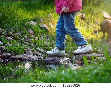 The child's legs in jeans and sneakers walking on stones across a stream