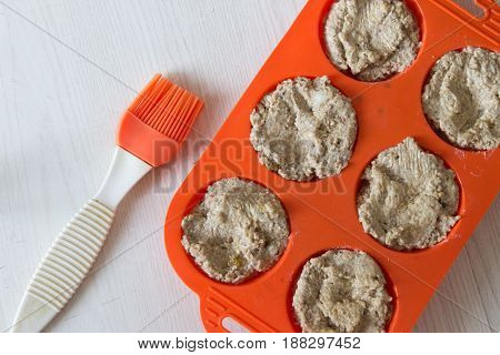 The process of making bread from rye flour with seeds. Bright orange silicone mold for cupcakes and brush. Top view.