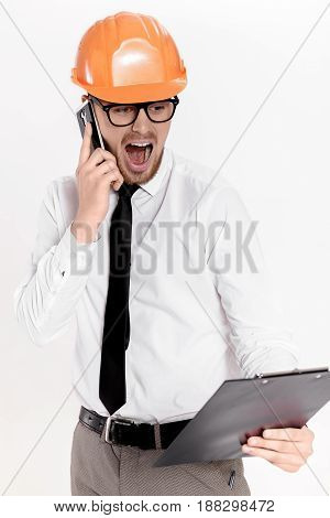 Young construction engineer in orange helmet with a folder talking on phone on a white background