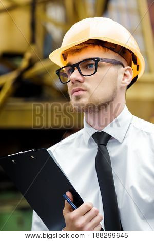 Engineer builder in a helmet holds folder at the construction site