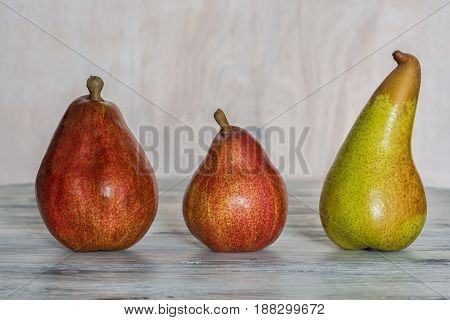 Three pears on a wooden white table .Pear red and yellow.
