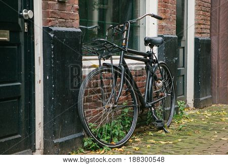 The bicycle is parked next to the house in Amsterdam in Europe. European style of life. A popular and eco-friendly means of transportation in Holland.