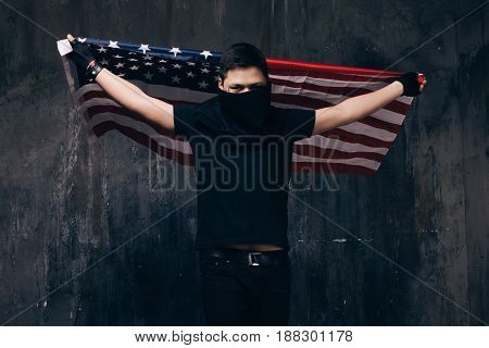 Flying USA flag and unrecognizable gangster. Guy in black cloth with hidden face on dark studio background. Riot, strike, bandit groups, disadvantaged youth concept