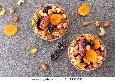 Two paper forms with mix of dried fruits and nuts over stone background. Top view