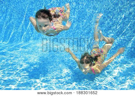 Children swim in pool underwater, happy active girls have fun in water, kids fitness and sport on active family vacation