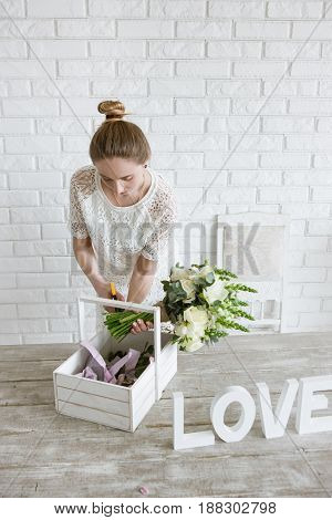 Decorator make flower bouquet. Young girl makes an ornament from white flowers in a workshop. Light florist studio with brick wall on background.