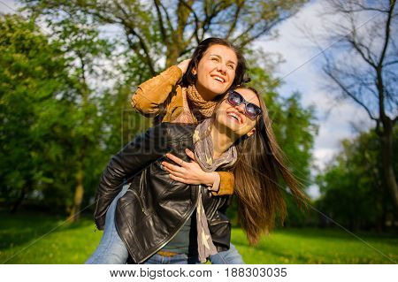 Two cute young women cheerfully spend time in the spring park. Women have a playful mood. Warm sunny day. Girlfriends enjoy the nature and communication.