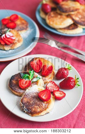 Ukrainian Syrniki Or Homemade Cheesy Pancakes With Mint And Strawberry On Beige And Blue Ceramic Pla