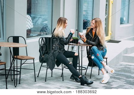 Two beautiful young women drinking coffee and gossiping in nice restaurant outdoor . The weather is great and sunny for walking rest relaxing spending time with best friends Friendship