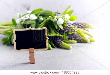 Tiny empty blackboard over blur flower background