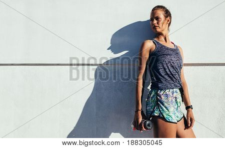 Portrait of young woman standing outdoors with water bottle looking away against a wall. Female runner relaxing after workout.