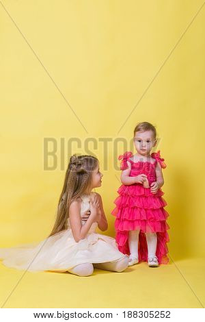 Two sisters in dresses on a yellow background in the Studio.