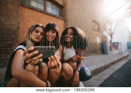Three Smiling Female Friends Making Selfie