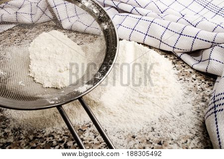 flour is sieved before baking with a metal sieve