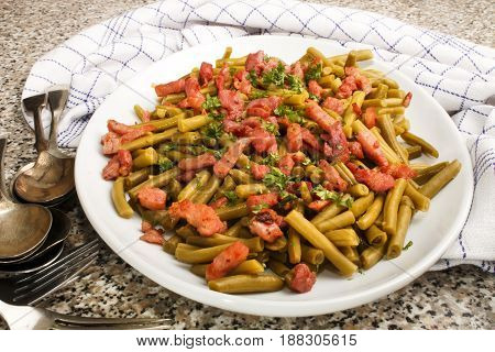 green beans with fried bacon and freshly chopped parsley on a white plate