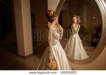gorgeous young blonde bride looking at the mirror at home