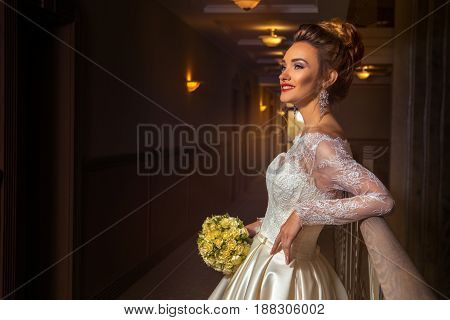 Cheerful young blonde bride smiling and looking aside in wedding dress